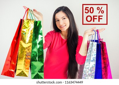beautiful happy brunette female with long hair shopaholic holding shopping bags . concept of shopaholism and 50% OFF sales