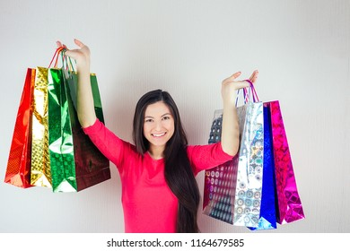 beautiful happy brunette female with long hair shopaholic holding shopping bags . concept of shopaholism and sales
