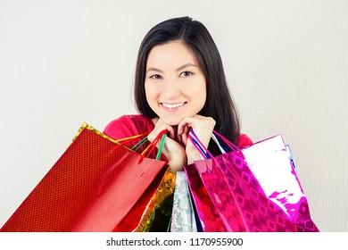 beautiful happy brunette female shopaholic holding shopping bags . concept of shopaholism and sales