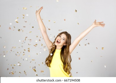 Beautiful happy brunette woman with long hair smiling and confetti falls everywhere. Time for a party