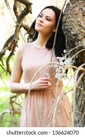 beautiful happy brunette woman in the park on a warm spring day with blossom flowers around her