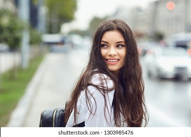 Beautiful happy brunette woman smiling outdoors on city street.