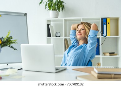 beautiful happy businesswoman with laptop at workplace in modern office