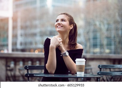 Beautiful happy businesswoman sitting in city park during lunch time or coffee break with paper coffee cup. Woman with coffee smiling outdoors.