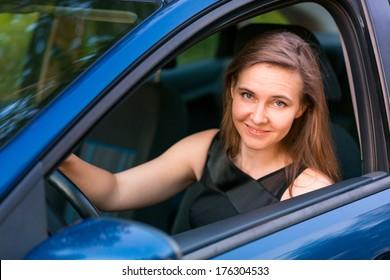 Beautiful happy businesswoman sitting in her car