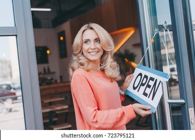 beautiful happy cafe owner holding sign open and looking away