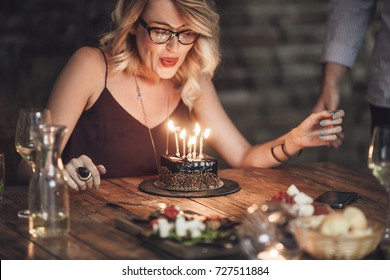 Beautiful happy Caucasian blonde woman blowing candles on birthday cake.