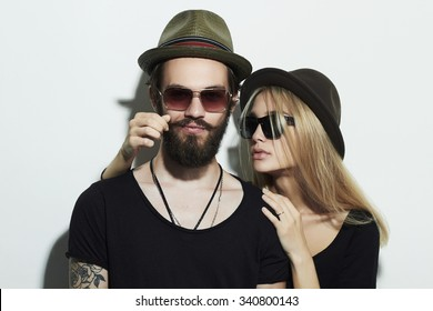 beautiful happy couple in hat wearing trendy glasses together. Hipster smiling boy and girl. Bearded young man and blonde model in sunglasses