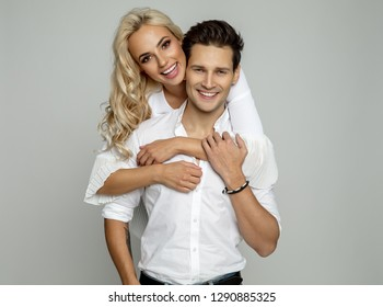 Beautiful happy couple hugging at each other isolated over gray background