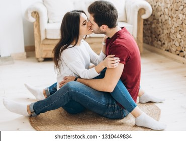 Beautiful and happy couple are kissing and hugging each other sitting on the floor on a small mat in a large light room