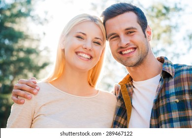 Beautiful and happy couple. Low angle view of beautiful young couple bonding to each other and smiling while standing outdoors