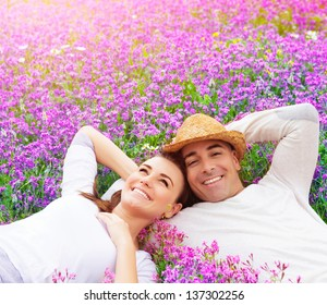 Beautiful happy couple lying down on purple lavender field, having fun on floral glade, summer nature, love concept