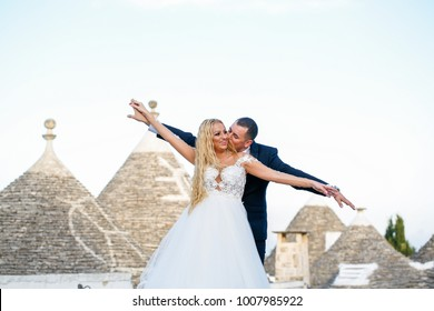 Beautiful happy couple posing on roof of old houses