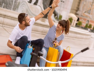 Beautiful happy couple pushing bicycle in the city and holding shopping bags. Urban Shopping concept.