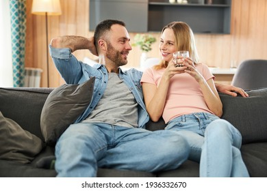 Beautiful happy couple sitting on sofa at home