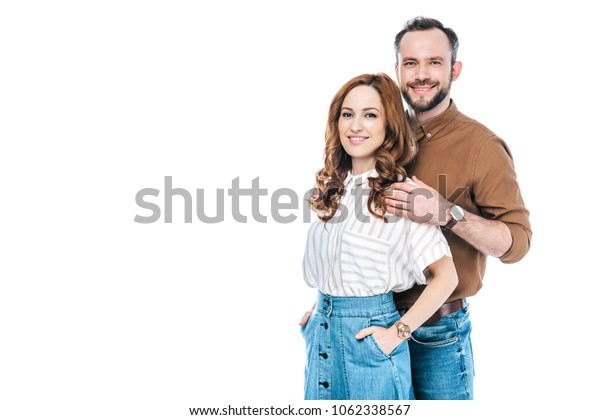 beautiful happy couple standing together and smiling at camera isolated on white