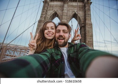 Beautiful happy couple taking selfie self-portrait on Brooklyn Bridge, New York. Hipster tourists having fun and photographing NY landmarks for travel blog.