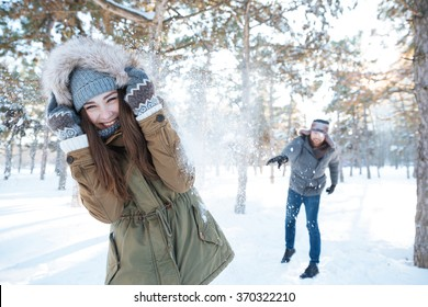 Beautiful happy couple throwing snowballs and having fun in winter park