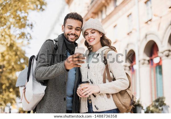 スマートフォンを使った美しい幸せな夫婦。秋に街で携帯電話を見ている若い喜びに満ちた笑顔の女性と男性。 テクノロジー、旅行、観光、学生のコンセプト