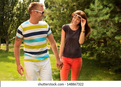 Beautiful happy couple walking in the park in sunny summer day.