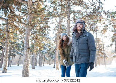 Beautiful happy couple in winter clothes walking outdoors in park