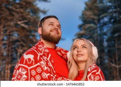 beautiful happy couple in winter forest cuddling