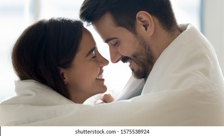 Beautiful happy couple young husband and wife bonding laughing covered with warm blanket, romantic affectionate lovers wrapped in duvet enjoying cozy morning lifestyle at home, close up profile view