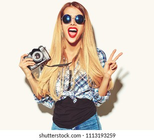 beautiful happy cute blond woman girl in casual summer hipster clothes with red lips takes photos holding retro photographic camera showing peace sign