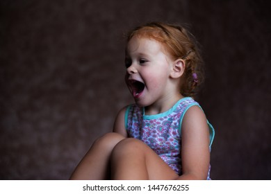 beautiful happy cute little redhead girl smiles sincerely and laughs with a soft light from the window lifestyle portrait