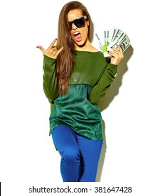 beautiful happy cute smiling brunette woman girl in casual green hipster summer clothes with no makeup isolated on white in sunglasses holding dollar and euro banknotes, showing rock and roll sign