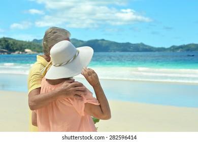 Beautiful happy elderly couple walking along the seashore