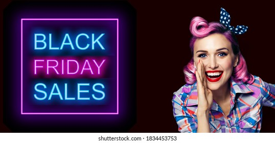 Beautiful happy excited woman holding hand near open mouth. Girl dressed in pin up. Blond model at retro fashion vintage advertising concept, over dark background. Black Friday sales neon light sign.
