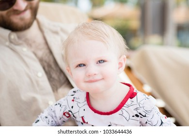 Beautiful Happy Expressive Blond Girl Toddler on the Beach with Sun Protection Sitting with her Father  in Mexico