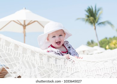 Beautiful Happy Expressive Blond Girl Toddler with Sun Protection in a Hamoock on the Beach in Mexico