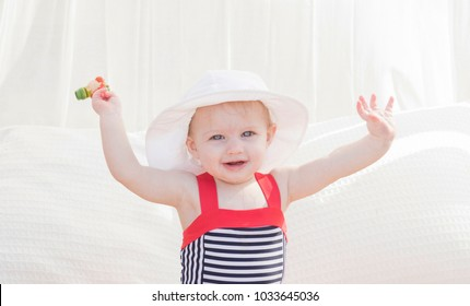 Beautiful Happy Expressive Blond Girl Toddler in a Cabana with Sun Protection on the Beach in Mexico