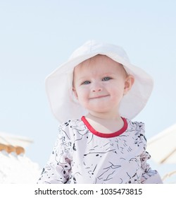 Beautiful Happy Expressive Blond Girl Toddler in a Hammock on the Beach with Sun Protection in Mexico
