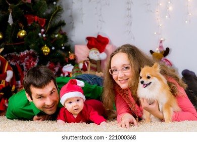 Beautiful happy family and the dog spending Christmas time at home near the Christmas tree. New year concept