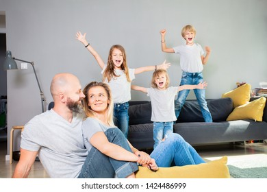 Beautiful and happy family having fun times at home. Cute kids playing while parents relaxing. Family spending time together in living room on weekend