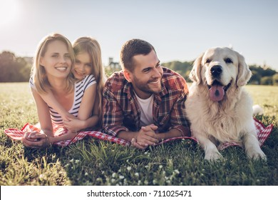 Beautiful happy family is having fun with golden retriever outdoors. Mother, father and daughter are lying with dog labrador on green grass in park.
