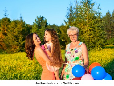 Beautiful happy family  outdoors during sunset with balloons, mother daughter child kid and sister grandmother