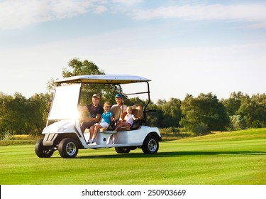 Beautiful happy family portrait in a cart at the golf course
