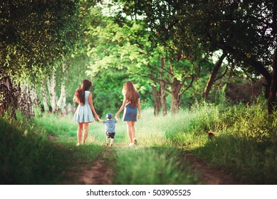 Beautiful happy family resting in nature. Two women - mother and aunt are the boy's hand along the trail in the woods. soft focus