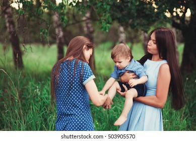 Beautiful happy family resting in nature. Two women - mom and aunt play with a boy in the Park. soft focus