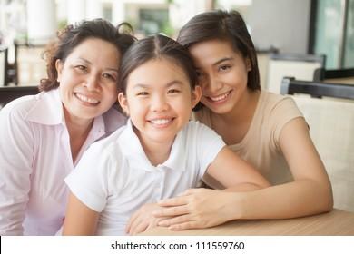 Beautiful happy family sitting at cafe and looking at camera