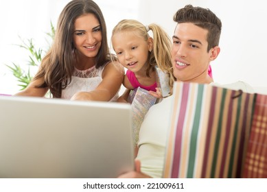 Beautiful happy family sitting at home with laptop and shopping bags.