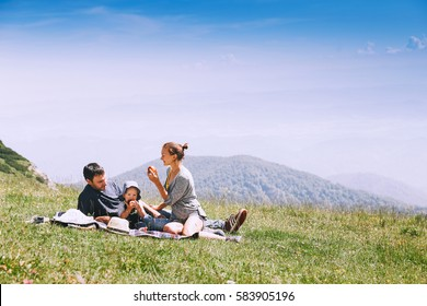 Beautiful happy family spends time on nature in the mountains. Family background. Lifestyle, Travel concept. Parent and child together. Velika Planina or Big Pasture Plateau in Kamnik Alps, Slovenia