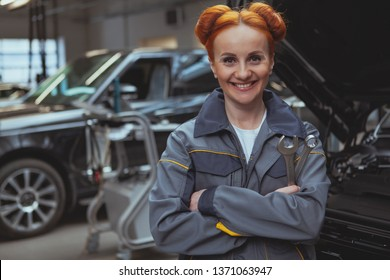 Beautiful happy female car technician posing proudly at her car service station, copy space. Charming woman enjoying working at the garage, repairing modern cars. Professionalism, experience concept