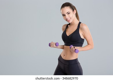 Beautiful happy fitness girl in sportwear holding dumbbells isolated over grey background