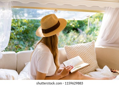 Beautiful happy girl in bed in the morning by the window of a van with a book. Dreams of life, reflects on the future, mental health and awareness