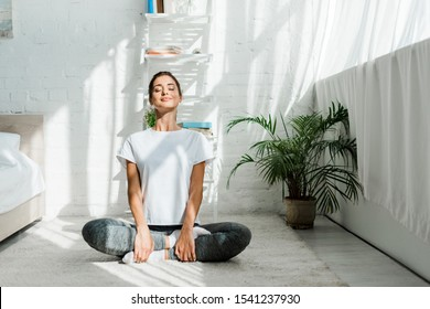 beautiful happy girl with closed eyes practicing yoga in lotus position in bedroom in the morning  - Shutterstock ID 1541237930